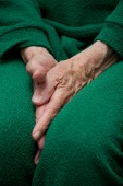 Old woman's hands tucked between her legs